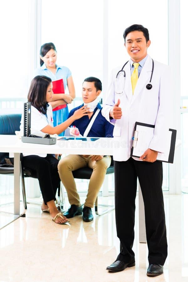 Contrôle asiatique de docteur sur le patient image stock