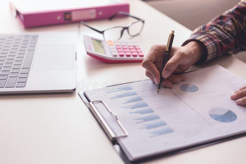 Contrôle d'homme d'affaires au sujet de coût et de faire le rapport de graphique de finances au bureau images libres de droits
