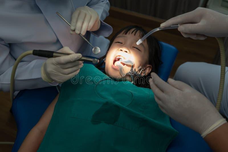 Contrôle de dents au bureau du ` s de dentiste Dents de examen de filles de dentiste dans la chaise de dentistes photo stock