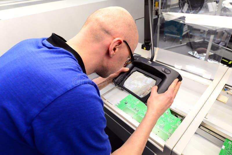 Contrôle de qualité dans la production - l'homme examine le conseil pour déceler les défauts images stock
