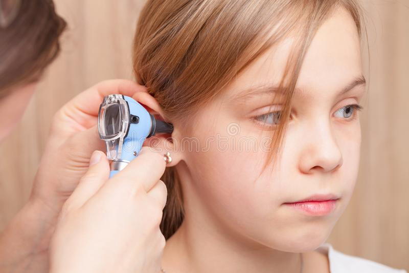 Contrôle OTO-RHINO d'enfant - oreille de examen de docteur de la fille élémentaire d'âge avec l'otoscope images libres de droits