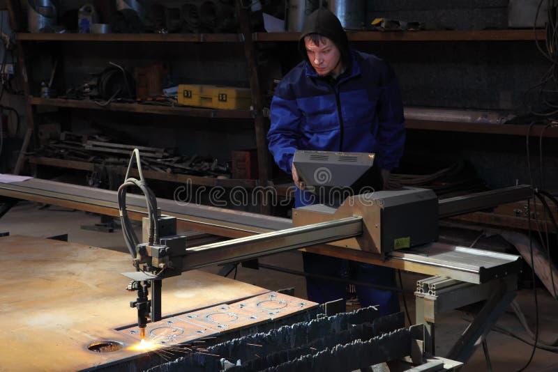 Contrôles d'un opérateur le processus de la coupe en métal de plasma photo libre de droits