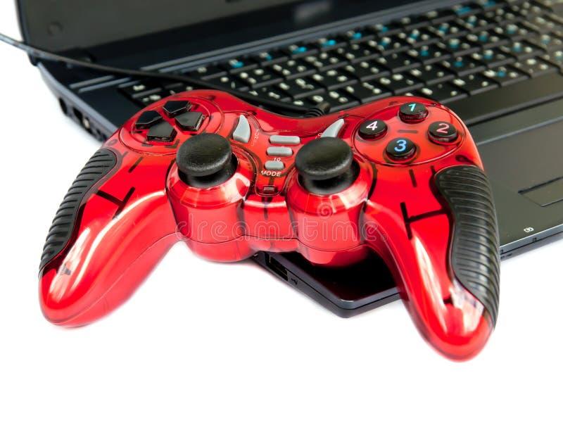 Contrôleur rouge de jeu de manche sur l'ordinateur portatif. image stock