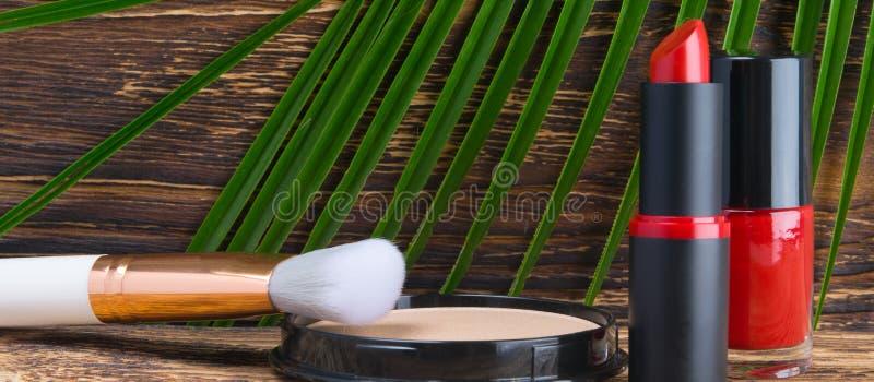 Contra la perspectiva de una tabla de madera oscura y de una hoja verde de una palmera, de un primer, de un esmalte de uñas rojo, fotografía de archivo