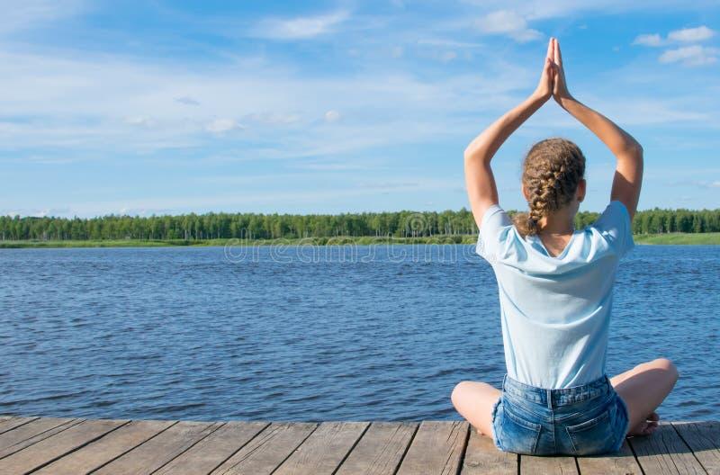 Contra o céu, a menina que senta-se no cais, fazendo a ioga, fora imagens de stock royalty free
