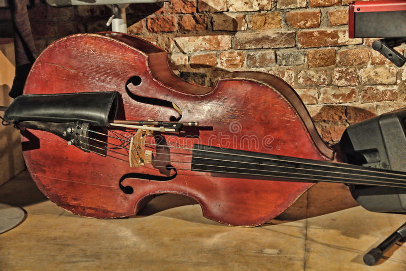 Contrabass on concert stage near old brick wall. Retro style toned image stock images