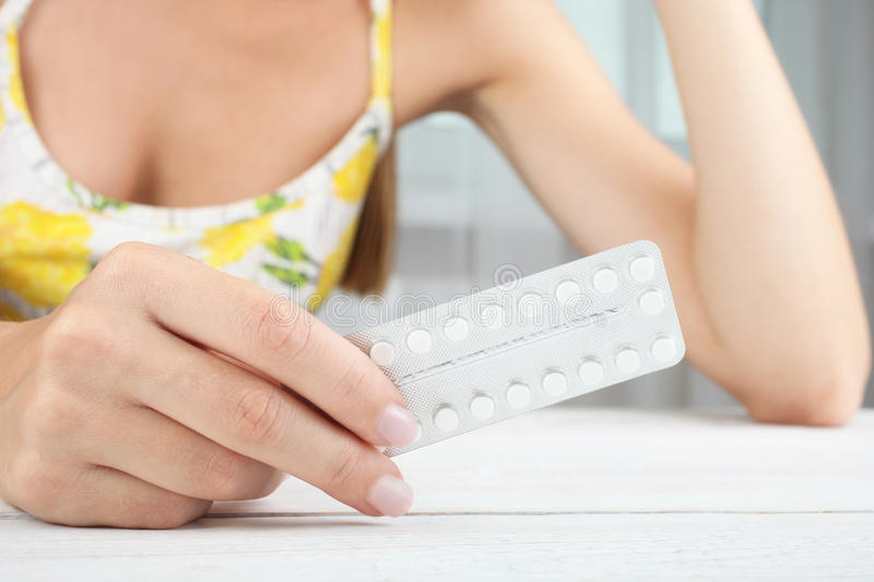 Contraceptive pills. Girl with contraceptive pills on the window background royalty free stock image