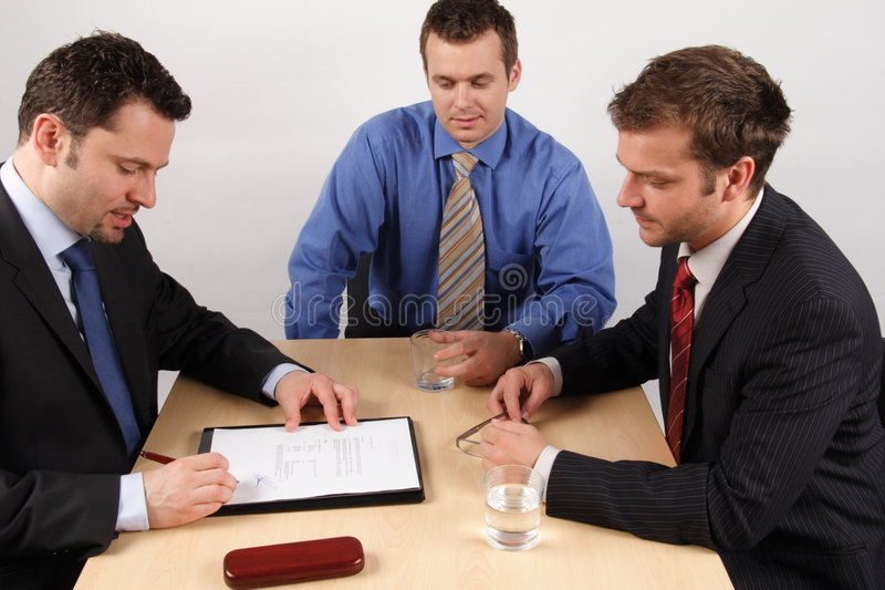 Contract. Three businessmen sitting at a table negotiating and signing a contract royalty free stock image