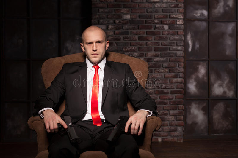 Contract assassin wallpaper, background or poster. Concept. Bald killer in suit and red tie sitting in a chair and holding pistols in hands stock photo