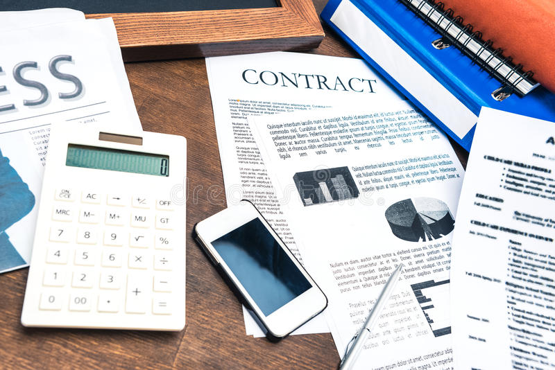 Contract documents, smartphone, calculator and business items. On wooden tabletop royalty free stock photo