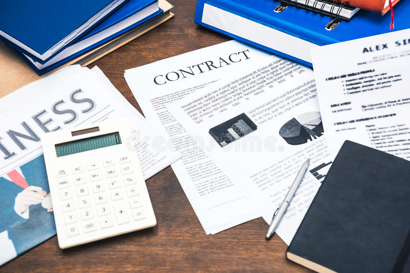 Contract documents, smartphone, calculator and business items. On wooden tabletop stock images