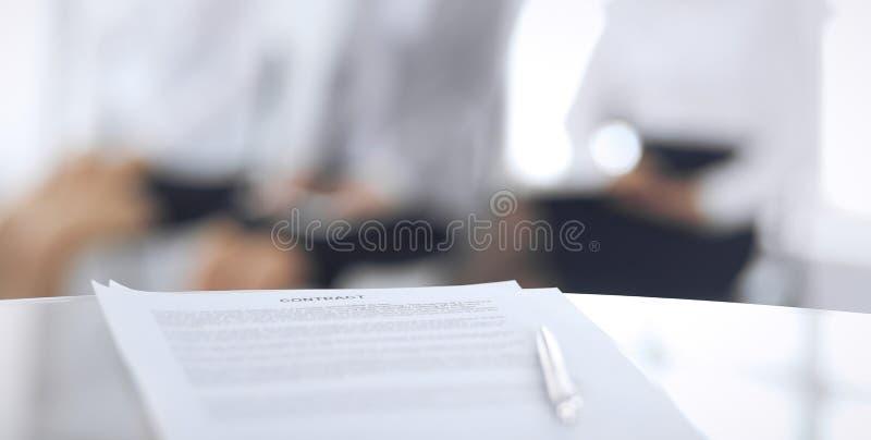 Contract met een pen en vage bedrijfsmensen op de achtergrond, close-up Vrouwelijke kandidaten die op gesprek wachten bij stock fotografie