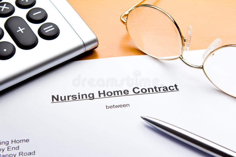 Contract nursing or retirement home. A contract for a nursing or retirement home with calculator, reading glasses and ballpoint pen royalty free stock photos
