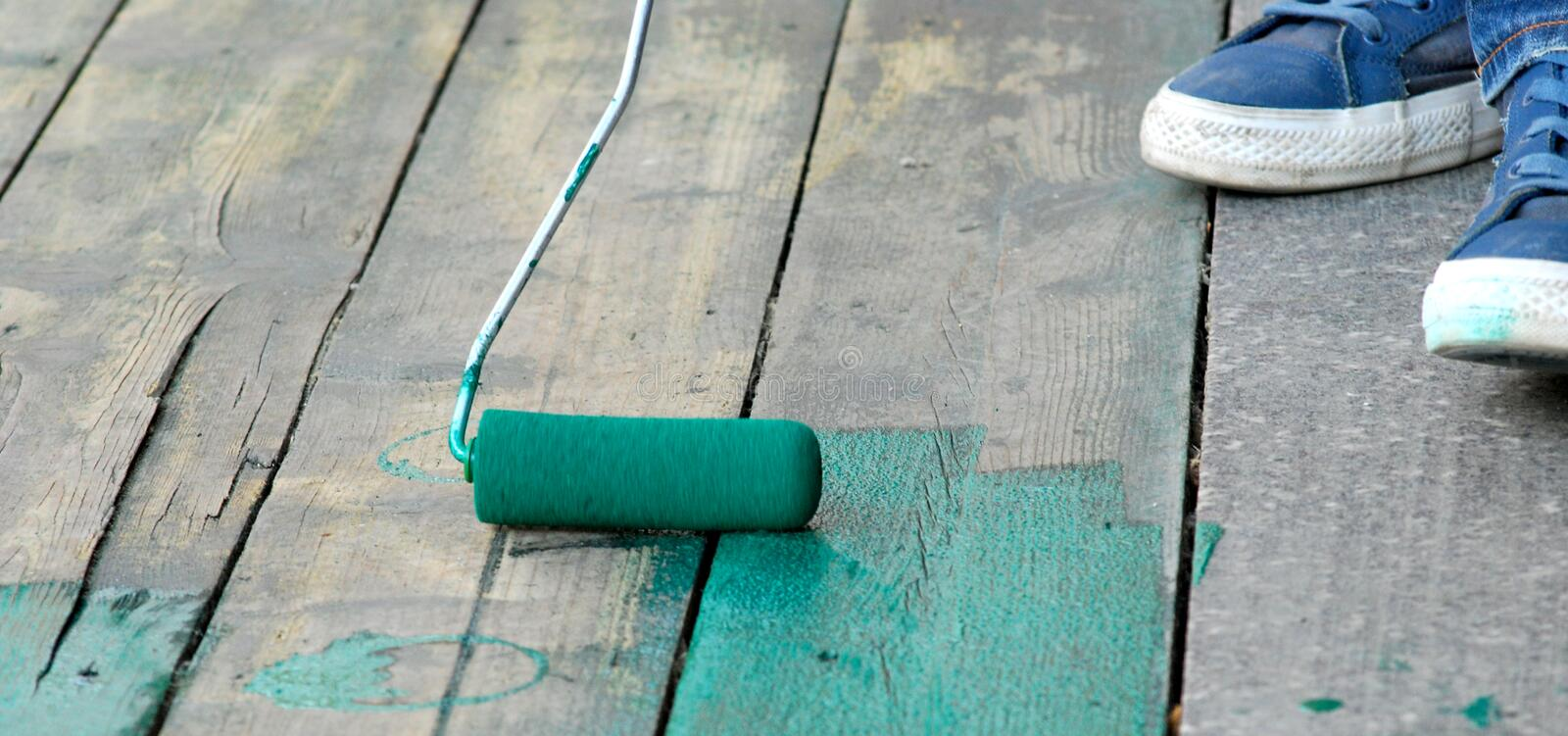 Contract painter painting a floor with green paint. Contract painter painting old wooden floor with green paint for waterproofing royalty free stock image