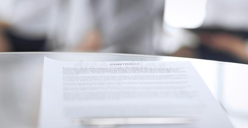 Contract with a pen and blurred business people on the background, close-up. Female candidates waiting for interview at royalty free stock images