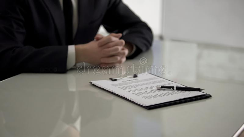 Contract with pen lying on table, male job applicant on background, employment royalty free stock image