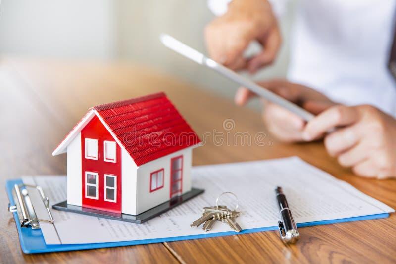 Contract van de het huislijst van de onroerende goederenmakelaar het woon, Bespreking met een makelaar in onroerend goed stock foto