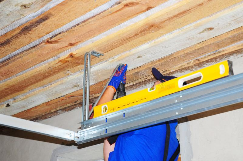 Contractant die de opener van de garagedeur met de houder van het metaalkader installeren stock foto's