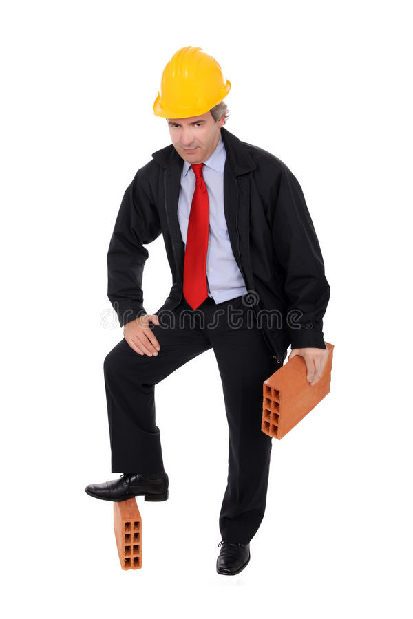 Contractor. A middle-aged contractor standing with one leg on a brick and holding another, isolated one white studio background stock images