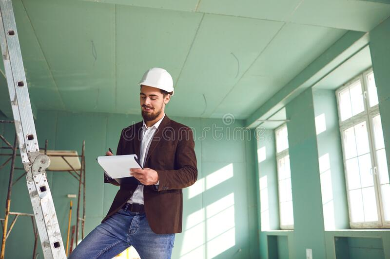 Contractor bearded man in a white helmet in a room at a construction site royalty free stock photography