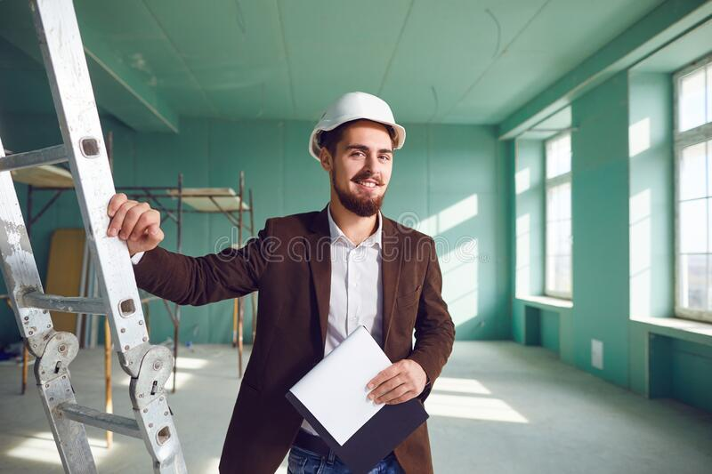 Contractor bearded man in a white helmet in a room at a construction site stock photo
