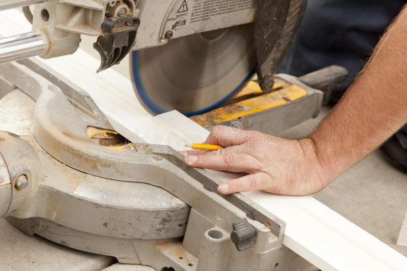 Contractor Cutting New Baseboard for Renovation. Contractor Using Circular Saw Cutting New Baseboard for Renovation royalty free stock photos