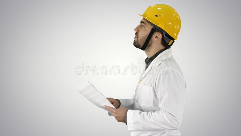 Contractor engineer walking with papers and checking arround on gradient background. stock photos