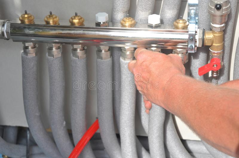 Contractor installing, repair floor heating system with insulated metal pipes. Contractor hand installing, repair floor heating system with insulated metal stock photo