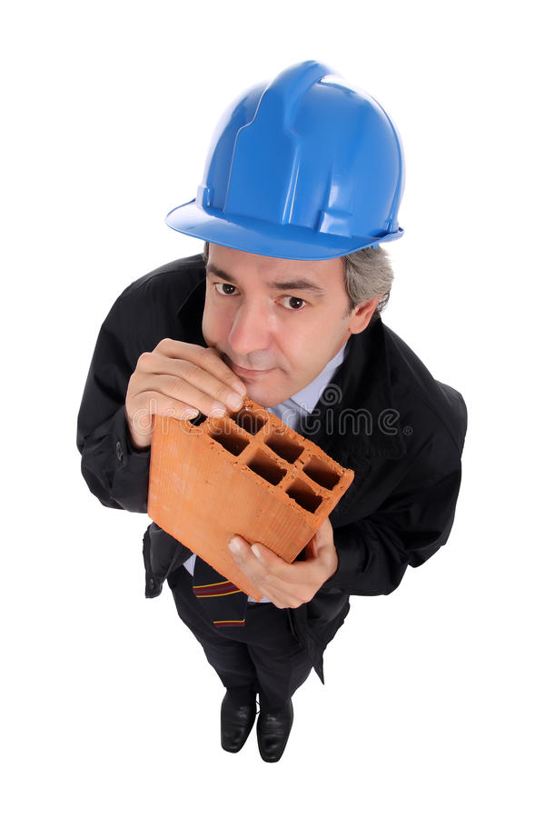 Contractor holding brick. A male contractor holding a brick and wearing a blue hard hat stock images