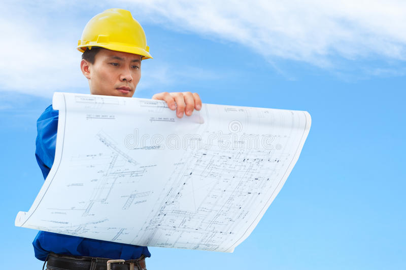 Contractor holding building plan. Contractor holding blueprint with blue sky background stock images
