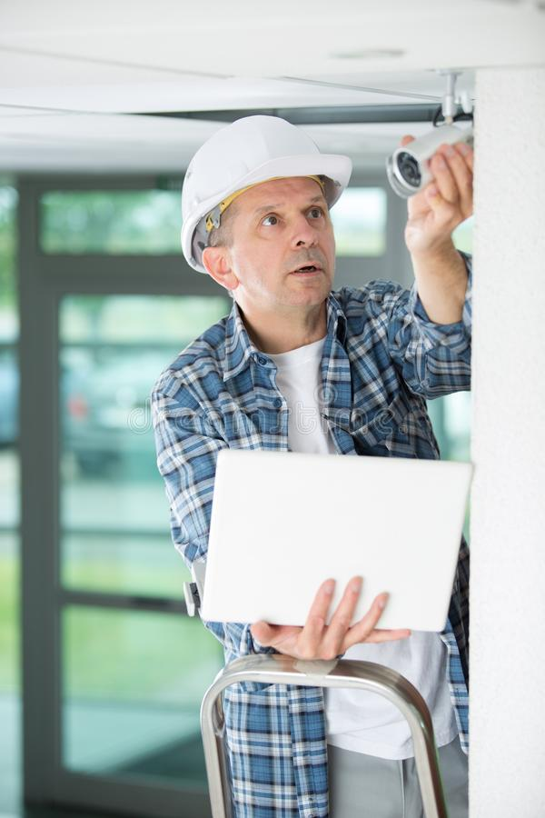Contractor holding laptop and surveillance camera royalty free stock image