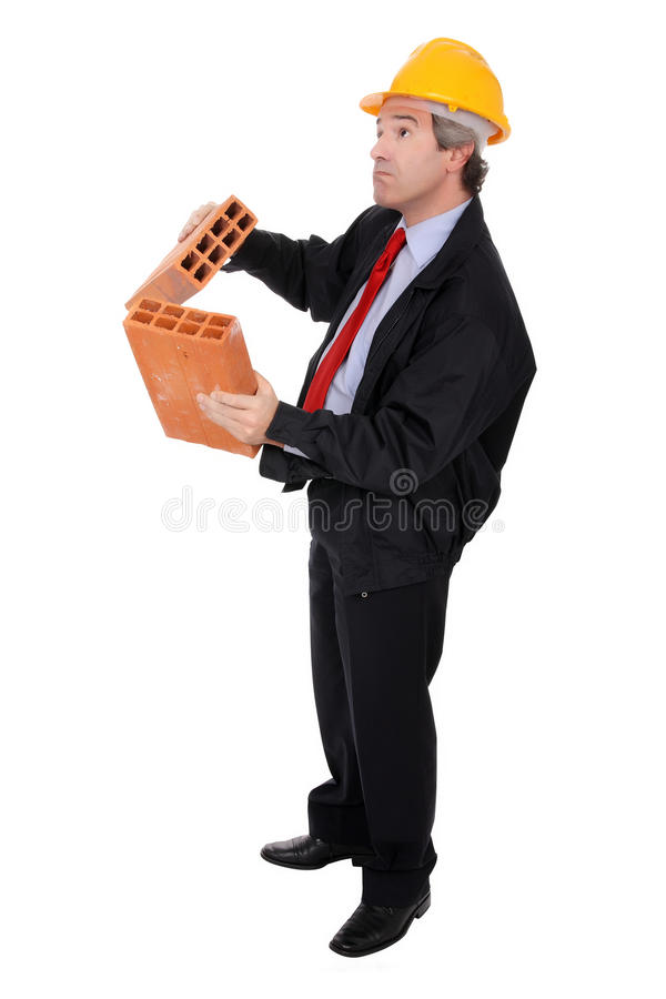 Contractor holding two bricks. Male contractor or foreman wearing yellow hard hat holding two bricks isolated against a white background stock photos
