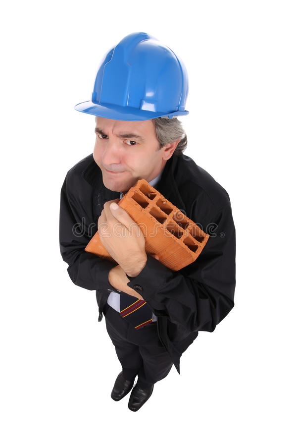 Contractor hugging brick. High angle view of suspicious middle aged contractor in safety helmet hugging brick, isolated on white background stock images