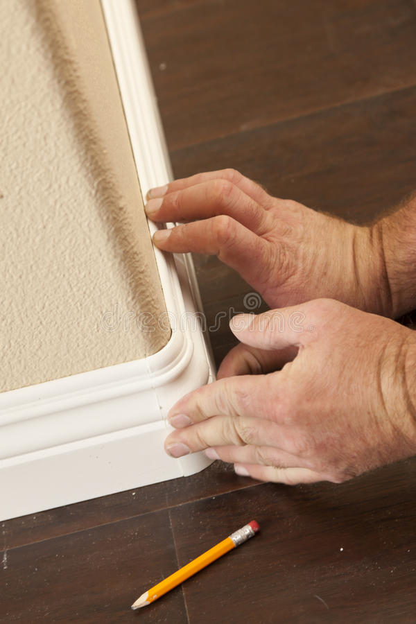 Contractor Installing New Baseboard with Bull Nose Corners and N. Ew Laminate Flooring Renovation Abstract stock images