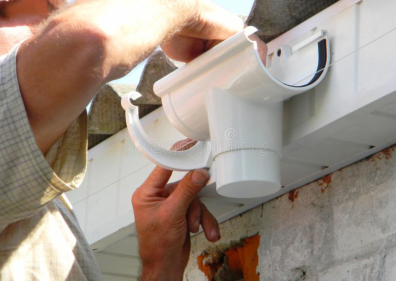 Contractor installing plastic roof gutter holder for dowspout drain pipe. Plastic Roof Guttering, Rain Guttering & Drainage royalty free stock images
