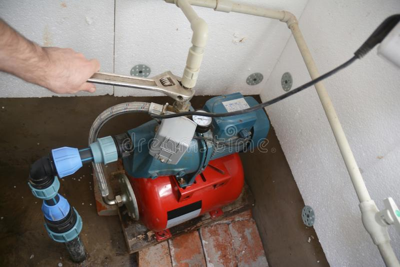 Contractor installing and repair water pump station. Borehole water pump. royalty free stock photography