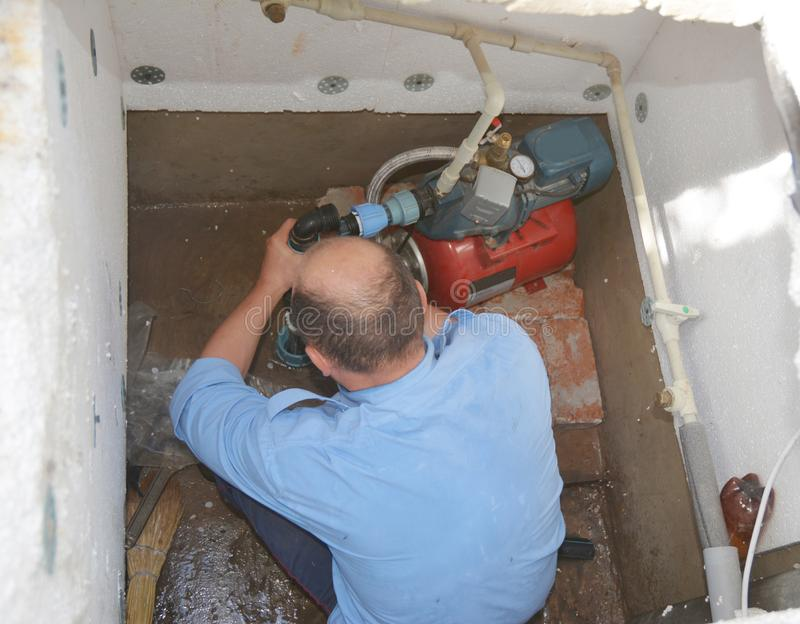 Contractor installing and repair water pump station. Borehole water pump stock photos