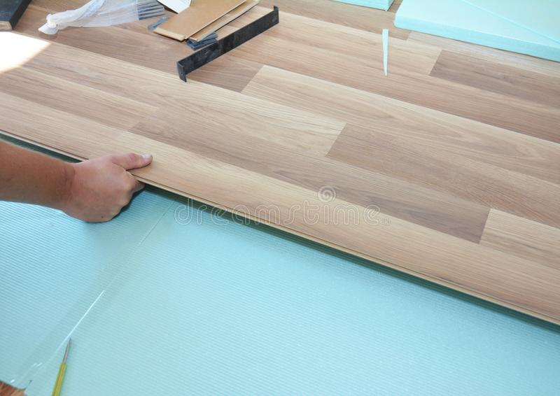 Contractor installing wooden laminate flooring with insulation and soundproofing sheets. Man laying laminate flooring. stock photo