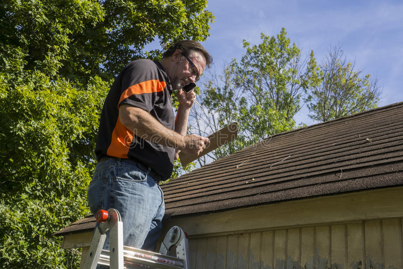 Contractor On Ladder Figuring Hail Damage Reairs To Roof. Contractor on ladder with cell phone figuring out hail damage repair costs for customer stock photo