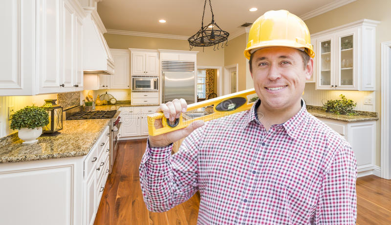 Contractor with Level Wearing Hard Hat Standing In Custom Kitchen royalty free stock photography
