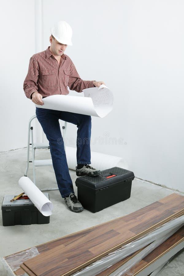 Contractor looking blueprints stock image
