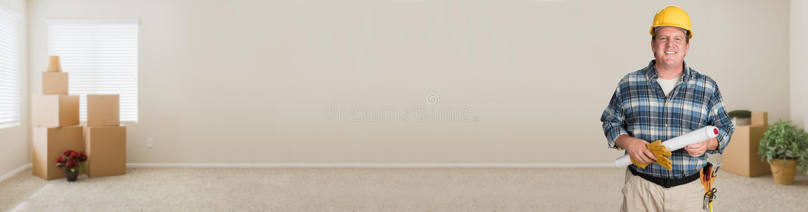 Contractor With Plans and Hard Hat In Empty Room with Moving Boxes royalty free stock photography