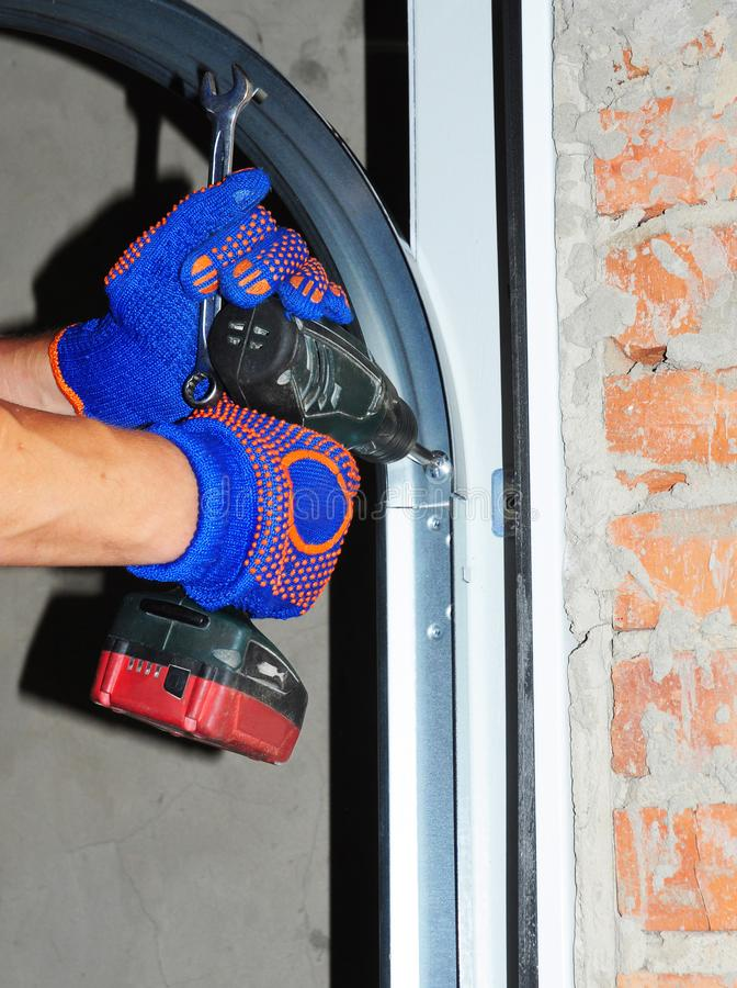 Contractor repair and install garage door. Replace a Broken Garage Door Spring. Contractor repair or install garage door. Replace a Broken Garage Door Spring royalty free stock image