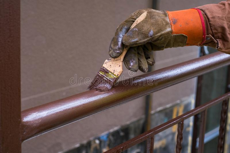 Contractor`s hand with brush that painting metal railing construction. Contractor`s hand with brush that painting metal railing construction stock image