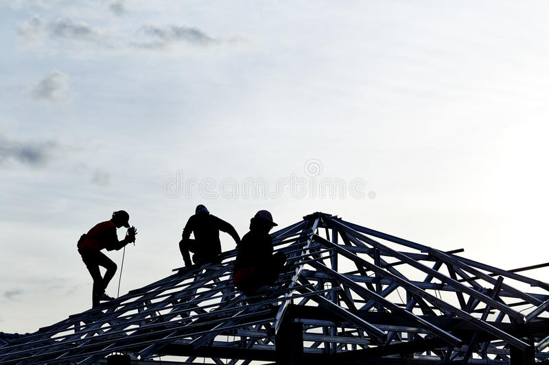 Contractor in Silhouette working on a Roof Top royalty free stock photos