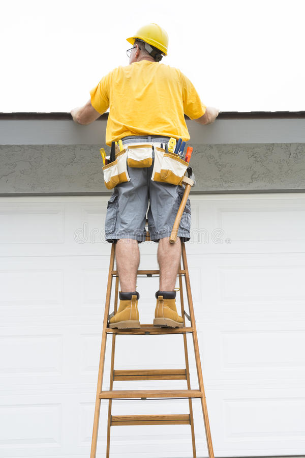 Contractor standing on ladder royalty free stock photo