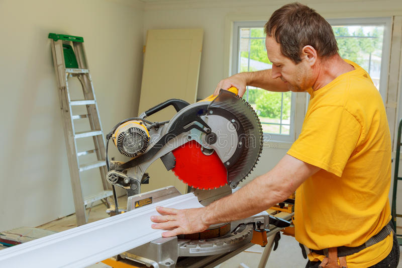 Contractor Using Circular Saw Cutting Crown Moulding for Renovation. Contractor Using Circular Saw Cutting New Crown Moulding for Renovation royalty free stock photography