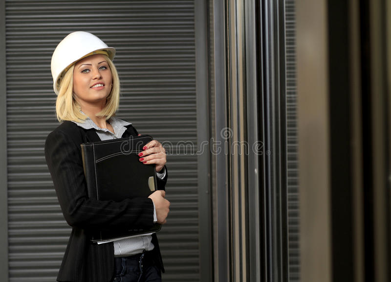 Contractor woman. Engineer or contractor woman with safety hat and leather folder in office environment stock photography