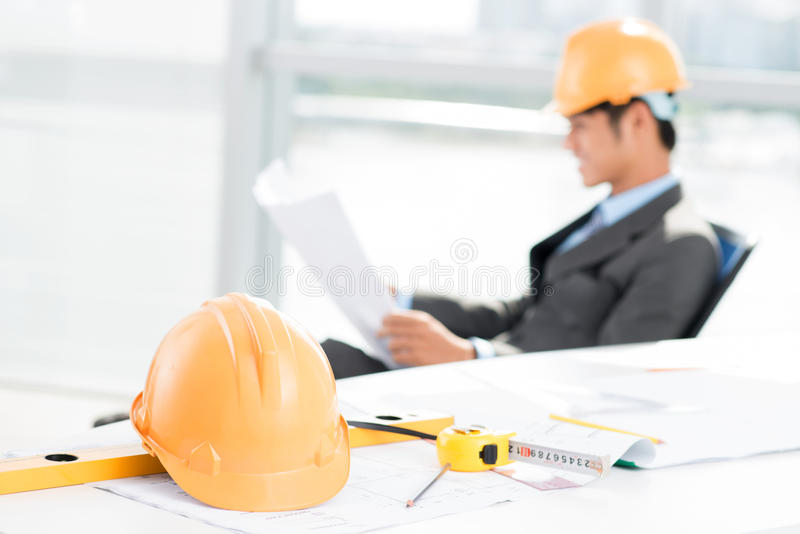 Contractor at work. Image of a working contractor with a hardhat and measuring tools in the foreground stock photography