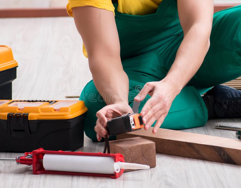 Contractor working on laminate wooden floor royalty free stock photos
